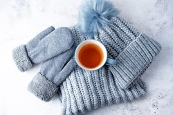 Winter Christmas holidays background with Cup of tea and wool hat, mittens and scarf. toning. selective focus