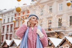 Winter, Christmas, New Year holidays concept: happy smiling woman walking at festive street fair with decorations. Model wearing blue beret, scarf, pink faux fur coat. Copy, empty space for text