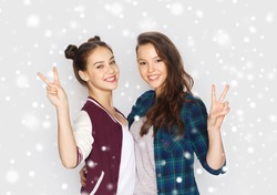 winter, christmas, people, teens and friendship concept - happy smiling pretty teenage girls or friends hugging and showing peace hand sign over gray background and snow