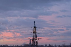 Winter city landscape. A beautiful sunrise, colorful clouds, an electrical cable support against a beautiful sky background.