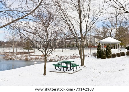 Winter city scene with a picnic table and gazebo at neighborhood recreation area.
