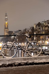 Winter cityscape with night view of snowy covered bicycles parked on canal bridge, Blurred architecture traditional canal houses and the Westerkerk church tower, Prinsengracht, Amsterdam, Netherlands.