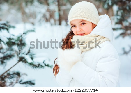 Winter close up portrait of cute dreamy child girl in white coat, hat and mittens playing outdoor in snowy winter forest. Traveling, vacation and active winter holidays concept