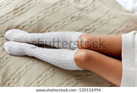 winter, clothes, fashion and people concept - close up of young woman legs in knee socks in bed at home #520156996