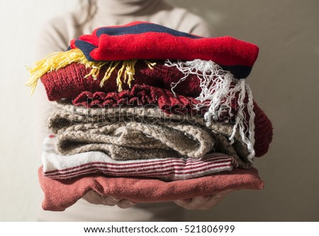 Winter clothes stacked in front of heater. #521806999