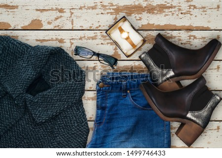 winter coat and blue jeans, golden hand watch with ankle boots and eyeglasses Women's spring summer basic outfit. Apparels flat composition