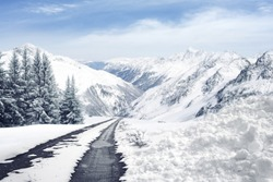 winter cold day with landscape of alps and road and sky and snow on top