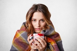 Winter cold sickness concept. Freezing beautiful woman wrapped in warm checkered plaid blanket, drinks hot beverage, tries to warm herself after spending time outside, home warm cozy atmosphere