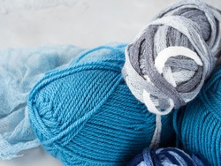 Winter color wool yarn with knitting needles. Blue palette and gray clews.
