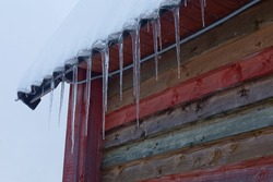 Winter composition. Icicles and snow on the roof. Colorful wall of a wooden house and dark gray sky. Horizontal composition