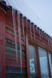 Winter composition. Icicles and snow on the roof. Colorful wall of a wooden house and dark gray sky. Vertical composition