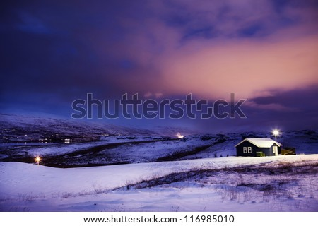 Winter Cottage in Snow with Dramatic Clouds at Night