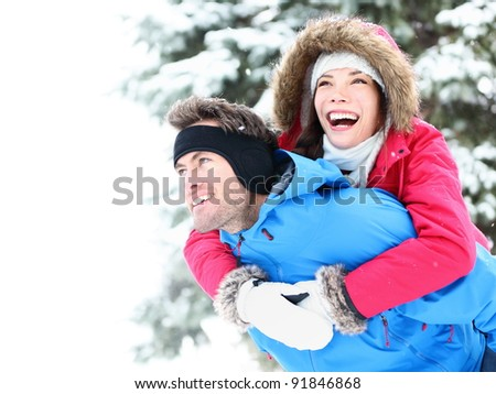 Winter couple piggyback in snow smiling happy and excited. Beautiful young multiracial couple, Asian woman, Caucasian man piggybacking