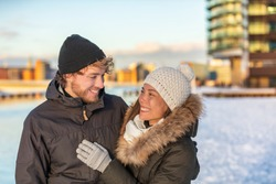 Winter couple walking happy in city wearing cold outerwear snow hat and jackets. Young biracial adults together smiling looking at each other on walk. Asian girlfriend in love with man.