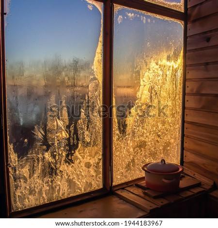 Winter dawn in frozen window. Frozen window winter sunrise