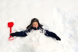 Winter day, a lot of snow, the child buried himself with a children's shovel around the neck in the snow.