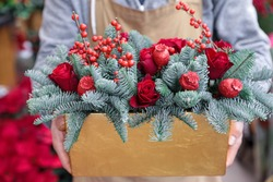 Winter decor. Beautiful flower arrangement of red roses, natural sprigs of blue spruce and Christmas berry holly or ilex twigs, brightly colored poppy heads for the winter festive home decor.