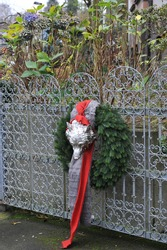 Winter decoration in a garden. A Christmas wreath made of conifers with a red bow  and a figure of a wolf's head on a metallic garden gate