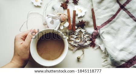 Photo of  Winter decoration, with lights, candle, fir branches and cones, hot coffee in a cup with marshmallows, with star anise on a black background. Christmas morning holiday concept. Flat lay. View from abo