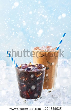 Winter drink iced coffee in a glass and ice coffee with cream in a tall glass surrounded by ice on white marble table over blue background with snow. Selective focus, copy space for text. #1274556535