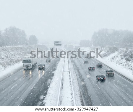 Winter Driving - commuter traffic on a highway - expressway - snowfall #329947427