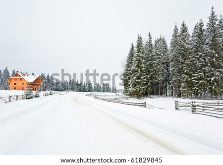 winter dull mountain landscape with  fence , wooden house and country road