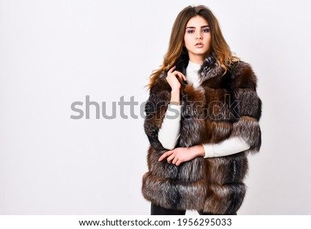 Winter elite luxury clothes. Female brown fur coat. Fur store model posing in soft fluffy warm coat. Pretty fashionista. Fur fashion concept. Woman makeup and hairstyle posing mink or sable fur coat