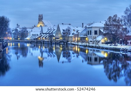 Winter evening in the snow covered old german town near Munich on the river Isar