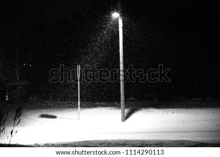 Winter evening scene. Falling snow illuminated by a streetlamp creates visual direction of light #1114290113
