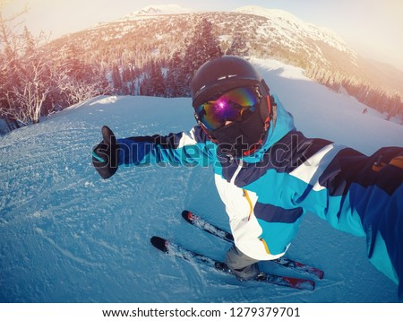 Winter extreme sport with selfie action camera. Man rides on slopes skis in protective helmet.