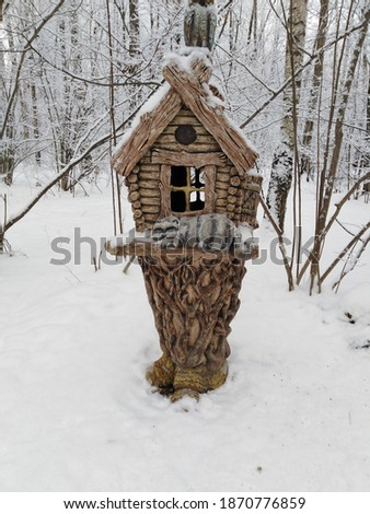 Winter, fairy-tale house for birds and squirrels.