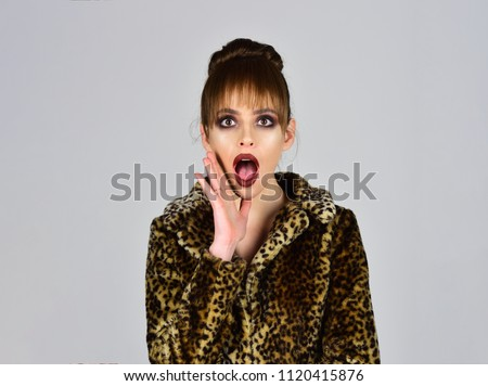 Winter fashion and beauty. Woman in leopard fur coat on grey background. Fur coat boutique with natural and artificial material. Look of fashion model with bad taste. Leopard fur at stylish girl