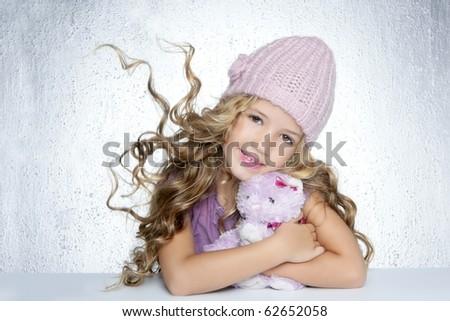 winter fashion cap little girl hug teddy bear smiling silver background