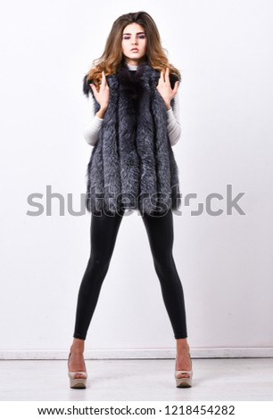 Winter fashion concept. Silver fur vest fashionable clothing. Girl makeup face long hairstyle wear fur vest white background. Fashion trend winter clothes. Luxury furry accessory. Boutique luxury fur. #1218454282