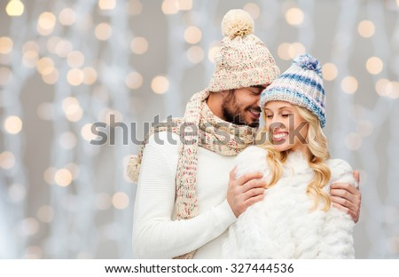 Stock Photo winter, fashion, couple, christmas and people concept - smiling man and woman in hats and scarf hugging over holidays lights background