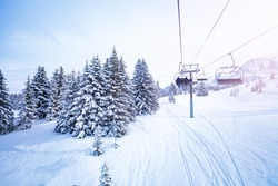 Winter fir and pine forest covered with snow after strong snowfall near ski lift on the mountain resort