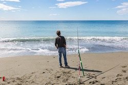 Winter fishing in the mediterranean sea. Fishing concept. Fisherman looks into the sea horizon standing near his fishing rod in rod holder with blue sea and cloudy sky background in sunny day