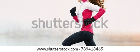 Winter fitness woman running in cold weather clothes wearing gloves and thermal pants, jacket jogging in white snow background landscape panorama banner.