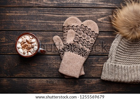 Winter flat lay with mitten, knitted hat and mug with hot chocolate or cocoa with marshmallow on dark rustic wooden table. Christmas and new year background. Overhead view #1255569679