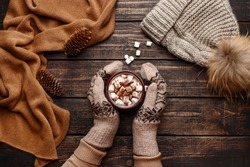 Winter flat lay with scarf, knitted hat and female hands in mitten holding mug with hot chocolate or cocoa with marshmallow on dark rustic wooden table. Christmas and new year background. Top view