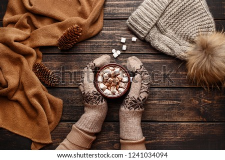 Winter flat lay with scarf, knitted hat and female hands in mitten holding mug with hot chocolate or cocoa with marshmallow on dark rustic wooden table. Christmas and new year background. Top view #1241034094