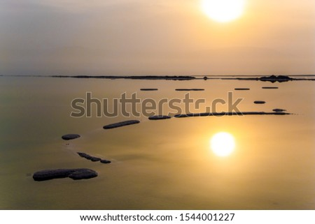 Winter foggy dawn. Dead Sea, Israel. Excess salt appears on the surface of the water. The sun is reflected in the water of the Dead Sea. Concept of ecological, medical and photo tourism