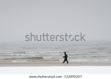 Winter foggy day, walker on the beach