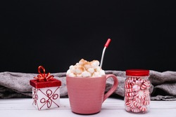 Winter food background. Cozy hot drink and treats. Christmas food background. Hot coco, metal straw and peppermint candies. Wooden background.
