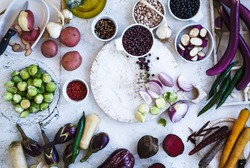 Winter food ingredients. Variety eggplants, colorful carrots, beetroot, potatoes, black and red beans, brussels sprout, herbs and spices on chopping board, over rustic white table. Top view.