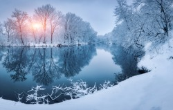 Winter forest on the river at sunset. Colorful landscape with snowy trees, river with reflection in water in cold evening. Snow covered trees, lake, sun and blue sky. Beautiful forest in snowy winter