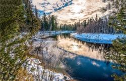 Winter forest river sunset scene. Sunset winter snow forest river. Forest river in winter sunset scene. Winter snow forest river sunset landscape
