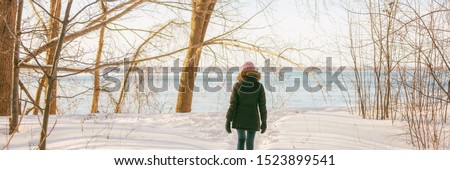Winter forest walk active woman walking in snow trail outdoor nature panoramic banner. Healthy lifestyle outdoors leisure activity panorama.