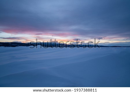 Winter frozen lake scene in northern Canada on a stunning cloudy sunset afternoon in March with white snow, mountains in background and iconic Canadian landscape in the north.