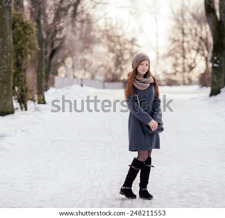 Winter full length portrait of a cute redhead lady in grey coat and scarf strolling in the park